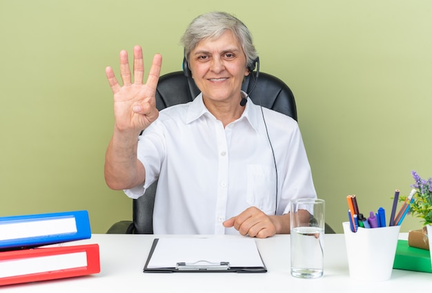Smiling caucasian female call center operator on headphones sitting at desk with office tools gesturing four with fingers