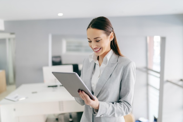 Smiling caucasian female ceo in formal wear and with long brown hair using tablet while standing at office. small opportunities are often the beginning of great achievements.