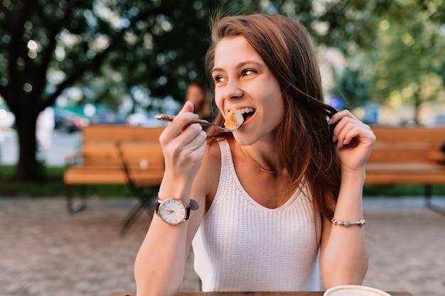 Modello femminile caucasico sorridente che mangia bigné fantasia nella caffetteria estiva all'aperto