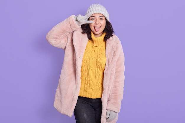 Smiling caucasian female model in yellow sweater, fur coat and cap, has pleased expression as poses against lilac wall. joyful girl showing v sign, shows tongue, expresses positive emotions.