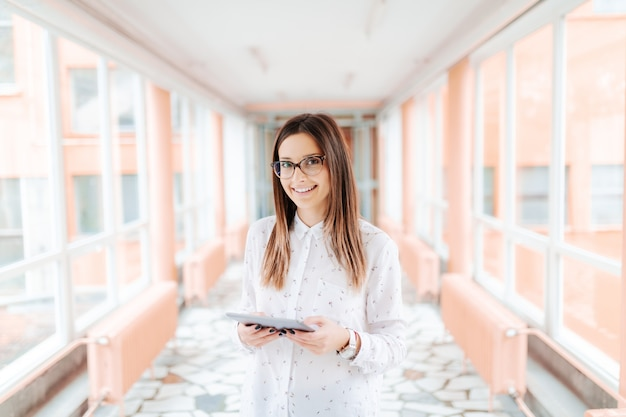 Smiling caucasian female teacher with eyeglasses using tablet while standing in the hall.