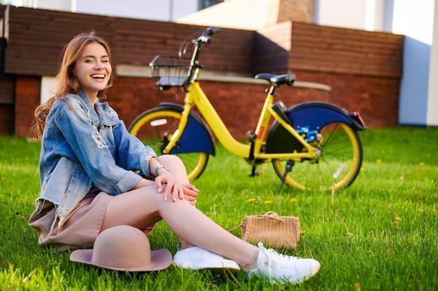 笑顔の白人女性(女性)がリラックスして、レンタルシティバイクの前の公園の芝生に座っています