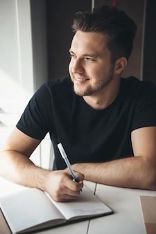 생각하고 집에서 창문을 통해 보면서 책에 뭔가 쓰는 백인 프리랜서 미소