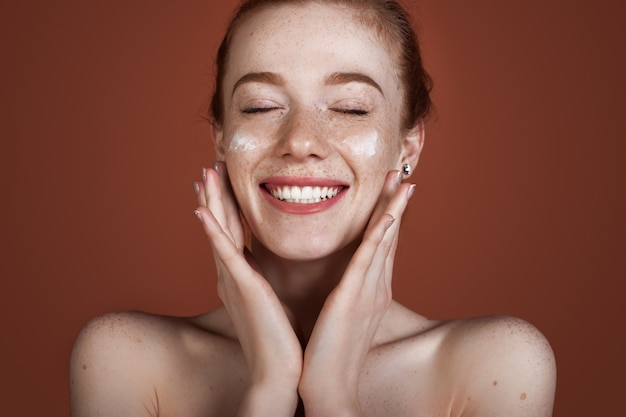Smiling caucasian ginger lady with freckles applying anti aging cream on face and smile posing with naked shoulders on red  wall
