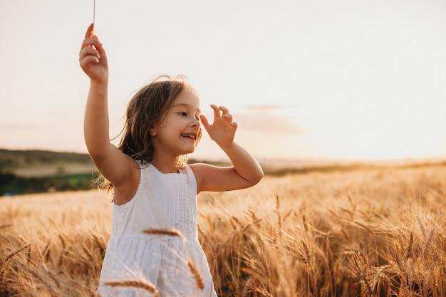Улыбающаяся кавказская девушка в белом платье ходит по пшеничному полю с веселой улыбкой на прыжках