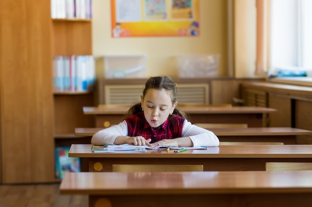 Smiling caucasian girl sitting at desk in class room and carefully reads the textbook.
