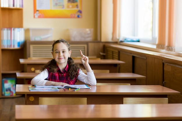 Smiling caucasian girl sitting at desk in class room and holding up her finger