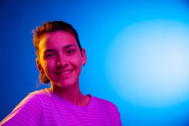 ネオンの光の暗いスタジオの背景に白人の幸せな若い女性の肖像画を笑顔