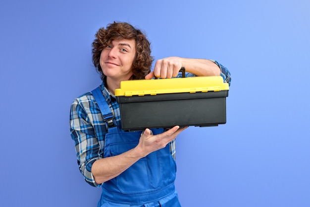 Smiling caucasian man in coveralls opening tool case box isolated on blue studio wall