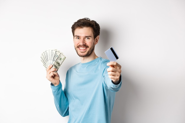 Smiling caucasian man holding money and giving you plastic credit card, standing on white background.