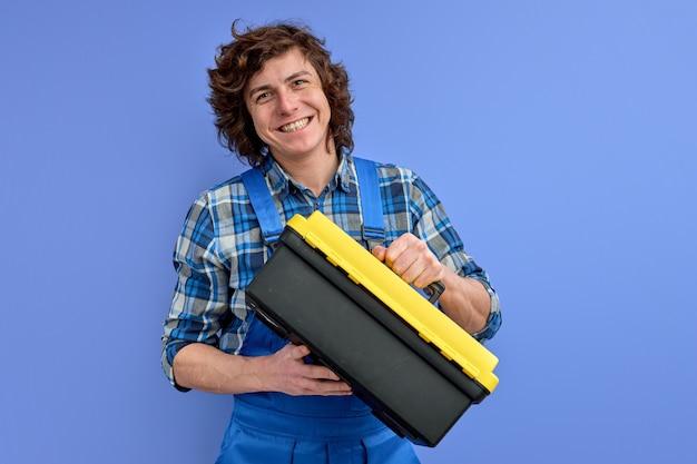 つなぎ服で笑顔の白人男性は、青いスタジオの壁に分離されたツールケースボックスを保持します
