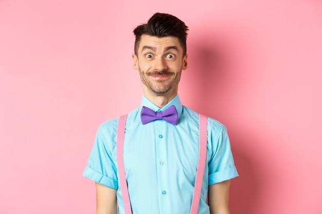 興奮しているように見える笑顔の白人男性、ロマンチックなデートのために上品な蝶ネクタイとシャツに立って、ピンク。