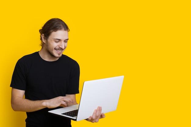 ひげと長い髪の笑顔の白人男性は、空きスペースのある黄色の壁にラップトップでポーズをとっています