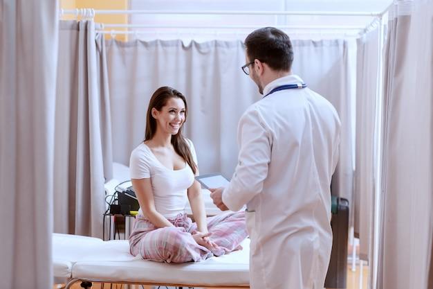 Улыбающийся кавказский пациент в пижаме сидит на больничной койке со скрещенными ногами и смотрит на врача. доктор держит таблетку и сообщает пациенту хорошие новости.