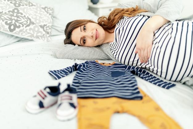 長い茶色の髪とベッドの上に横たわるストライプブラウスで白人の妊娠中の女性の笑顔