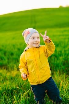 Улыбающийся кавказский дошкольник показывает жест победы на открытом воздухе
