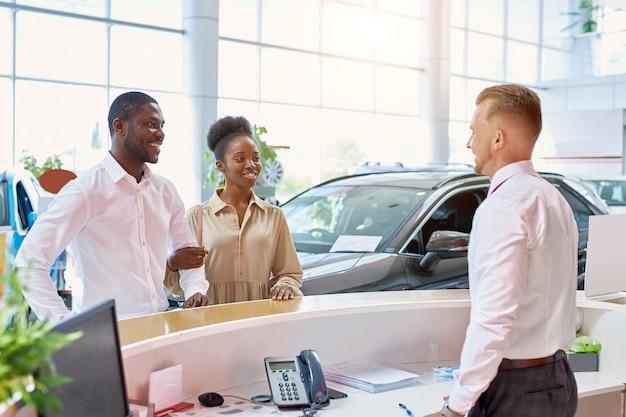 Улыбающийся кавказский эксперт по продажам приветствует клиентов в автосалоне
