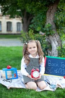 大きな赤い目覚まし時計と白人女子高生の笑顔は、学校の近くの公園の芝生でリラックスします。