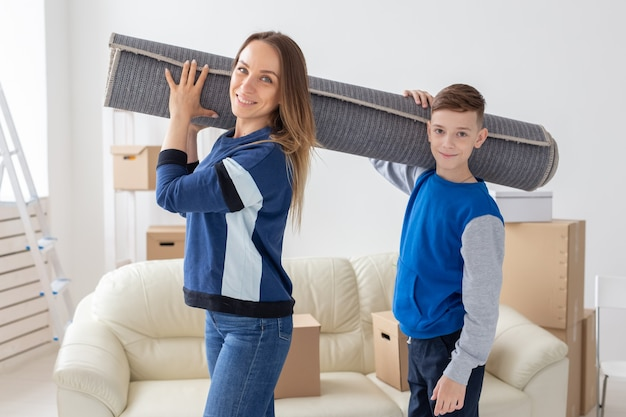 웃는 백인 미혼모와 매력적인 아들이 어깨에 접힌 카펫을 들고 있습니다.