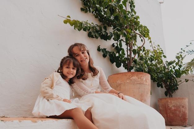 植物の隣に座っている茶色の髪の白人姉妹の笑顔
