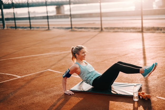 Smiling caucasian sporty blonde woman in blue sportswear listening music and doing exercises on mat on court. pain is temporary, greatness is forever.