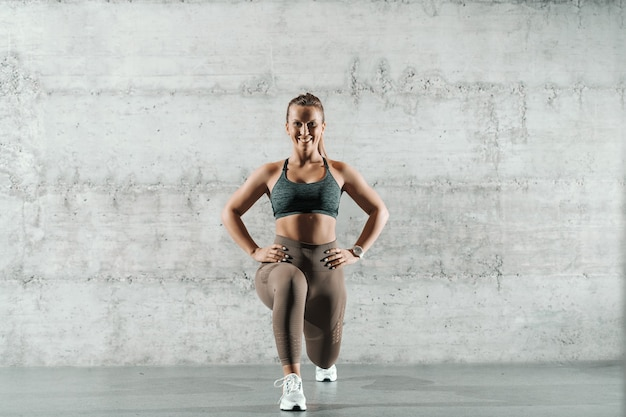 Smiling caucasian sporty woman dressed in sportswear and with ponytail doing lunges in the gym.