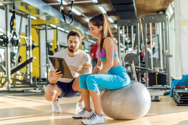 Smiling caucasian sporty woman sitting on pilates ball and looking at results of training that her personal trainer showing her. trainer crouching next to her.