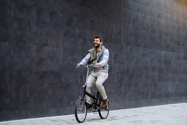 Smiling caucasian stylish bearded caucasian man listening music and riding his bicycle. in background is gray wall.