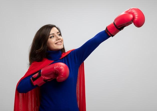 La ragazza caucasica sorridente del supereroe con il mantello rosso che indossa i guantoni da pugile sta con le mani alzate che guardano e che indicano al lato isolato sulla parete bianca con lo spazio della copia