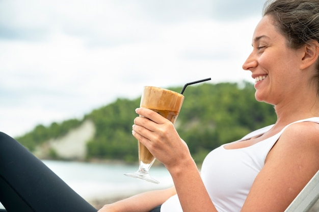 Smiling caucasian woman holding coffee drink on a beach with foam and drinking straw with hills