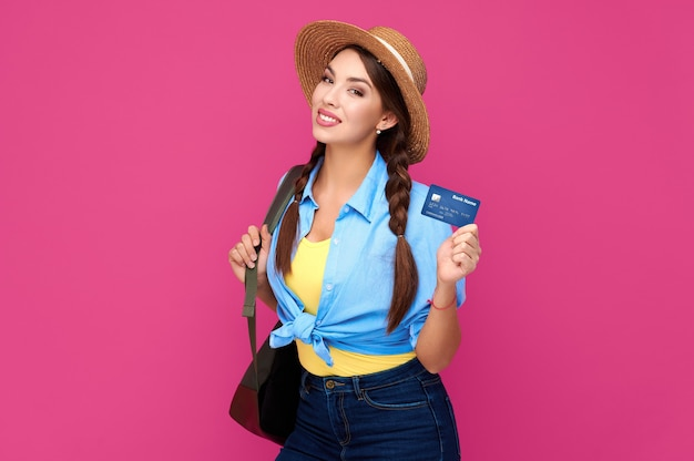 ピンクの背景で隔離のクレジットカードを保持している白人女性の笑顔。オンラインショッピング、eコマース、インターネットバンキング、お金を使う、人生の概念を楽しむ