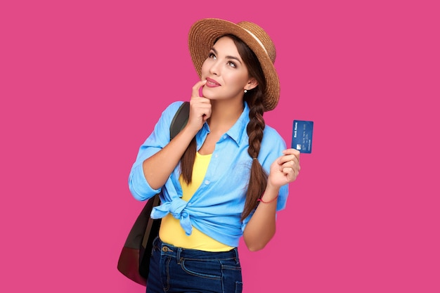 Smiling caucasian woman holding credit card isolated on pink background. online shopping, e-commerce, internet banking, spending money, enjoying life concepts