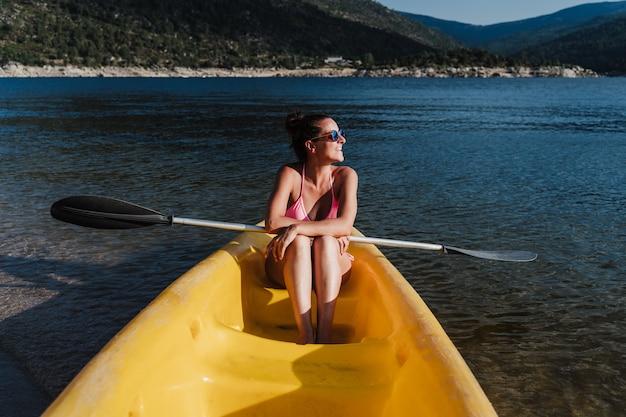 Улыбающаяся кавказская женщина, держащая весло, сидит на желтом каноэ в озере в солнечный день. летнее время. спорт, приключения и природа