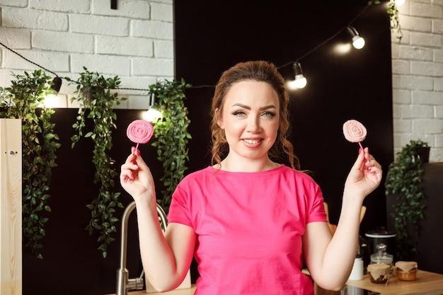 Улыбающаяся кавказская женщина в розовой футболке держит леденцы на палочке безе, в помещении на кухне.