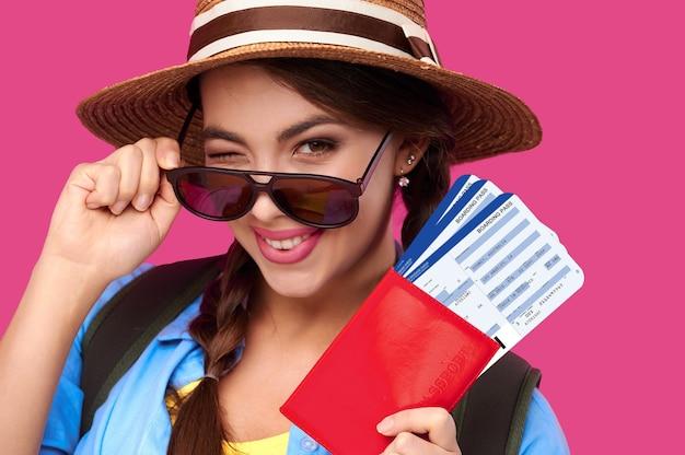 Улыбаясь кавказской женщины insunglasses держа паспорт с проездным билетом внутри на розовом фоне изолировать. студой выстрел