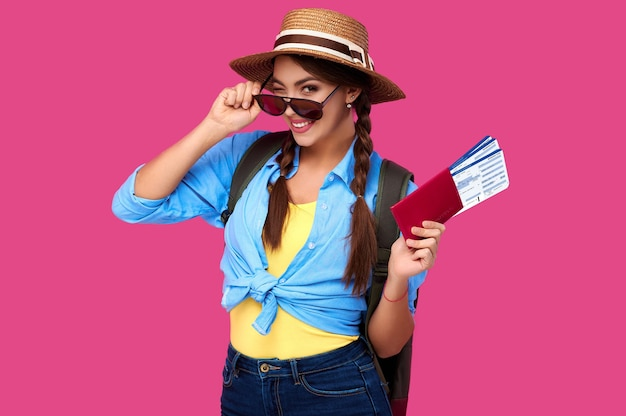 Smiling caucasian woman insunglasses holding passport with travel ticket inside over pink isolate background. studoi shot