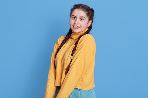 Smiling caucasian woman keeping hands together and looking directly at front, attractive brunette female wearing yellow sweater standing isolated over blue wall