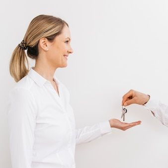 Smiling caucasian woman receiving keys from man