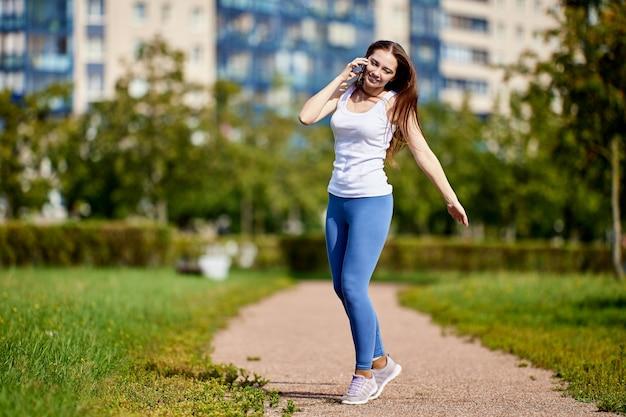 Улыбающаяся кавказская женщина разговаривает со смартфоном на открытом воздухе