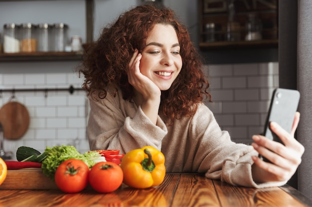 Улыбается кавказская женщина с помощью мобильного телефона во время приготовления салата из свежих овощей в интерьере кухни дома
