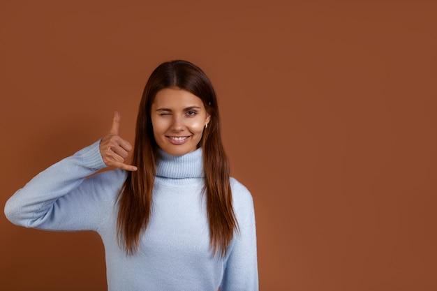 파란색 스웨터를 입고 웃는 백인 여자가 전화 제스처를 만들고 그녀에게 전화를 요청하고 눈을 깜박입니다.