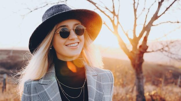 안경과 모자가 전면을보고 배경에 완벽한 일몰과 함께 포즈를 취하는 웃는 백인 여자