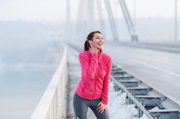 橋の上に立って休憩しながら音楽を聴くスポーツウェアに身を包んだポニーテールの白人女性の笑顔。冬の健康的なライフスタイルのコンセプト。