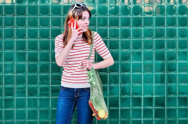 Улыбающаяся кавказская молодая девушка разговаривает по мобильному телефону с сетчатой сумкой через плечо с овощами на зеленой стене на улице