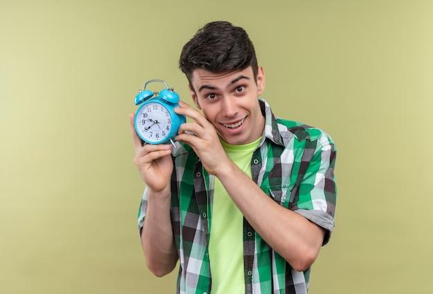 Ragazzo giovane caucasico sorridente che indossa la camicia verde che tiene sveglia intorno al fronte con entrambe le mani su fondo verde isolato