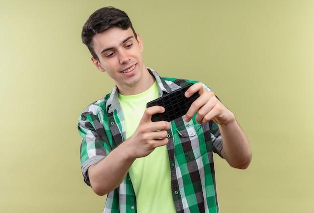 격리 된 녹색 배경에 전화 게임 녹색 셔츠를 입고 웃는 백인 젊은 남자
