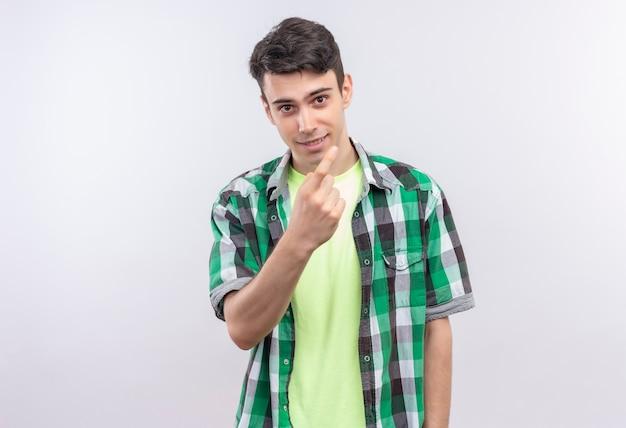 Улыбающийся кавказский молодой парень в зеленой рубашке показывает жест иди сюда на изолированном белом фоне