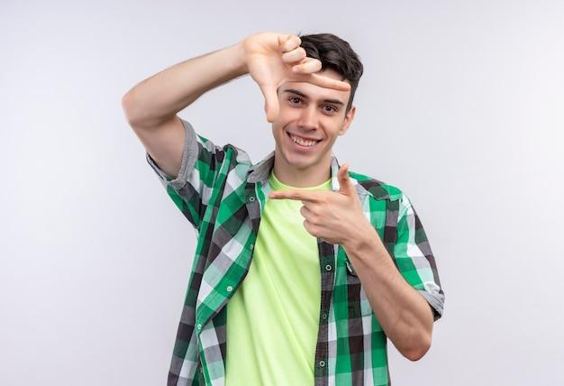 Ragazzo giovane caucasico sorridente che indossa la camicia verde che mostra gesto della foto su fondo bianco