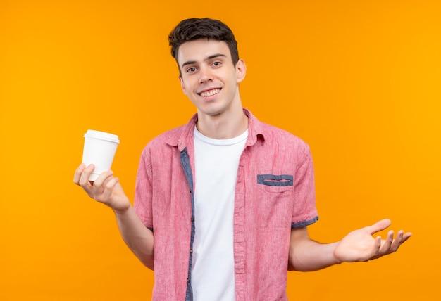孤立したオレンジ色の背景に手を上げたコーヒーのカップを保持しているピンクのシャツを着て笑顔の白人の若い男