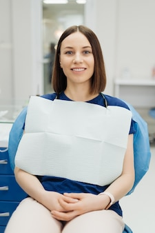 Улыбаясь кавказской молодой женщины пациента на медицинском осмотре стоматолога, сидя в кресле стоматологии, глядя на фронт